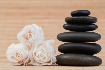 Close up roses and a black pebbles stack against bamboo background photo