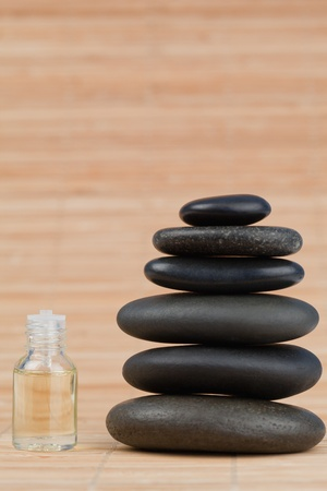 Glass phial filled in with pale yellow liquid and a stack of black pebbles against a bamboo background photo