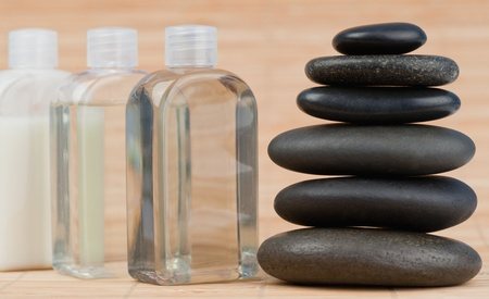 Close up of a glass flasks and a black stones stack photo
