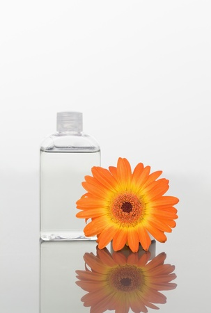 Orange gerbera and a glass flask on a mirror agains white back ground photo