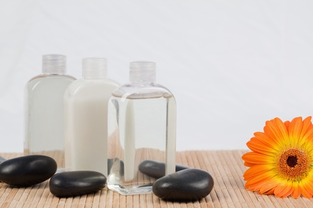 Sunflower with black stones and massage oil bottles photo