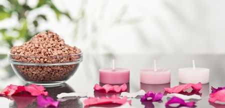 A bowl of brown gravel with pink petals and candles photo