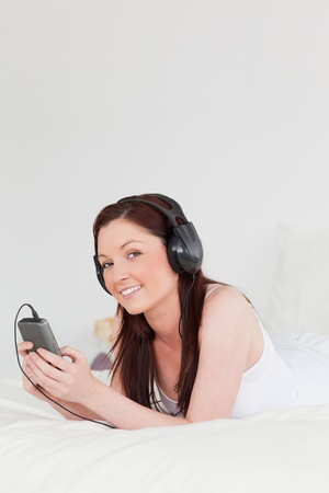 Gorgeous red-haired female listening to music with her headphones while lying on her bed  photo