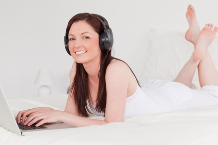 Beautiful red-haired female relaxing with her laptop and her headphones while lying on her bed photo