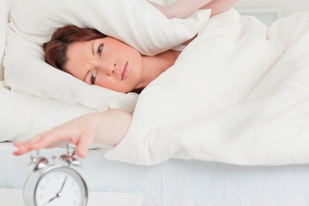 Charming red-haired woman waking up thanks to an alarm clock in the bedroom photo