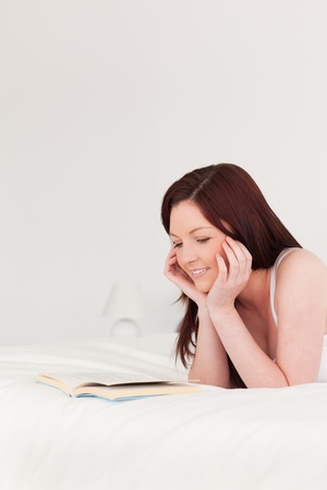 Pretty red-haired woman reading a book while lying on her bed photo