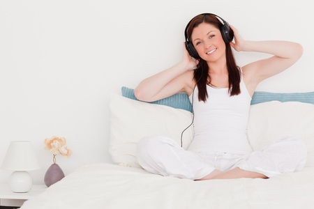Pretty red-haired woman listening to music with her headphones while sitting on her bed photo