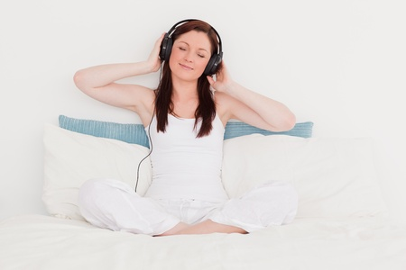 Happy red-haired woman listening to music with her headphones while sitting on her bed photo