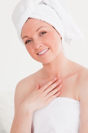 Pretty young woman wearing a towel against a white background photo