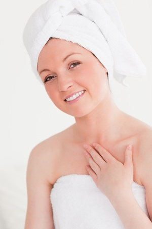 Gorgeous young woman wrapped in a towel against a white background photo