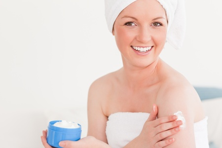 Beautiful young female wearing a towel using skin cream against a white background photo