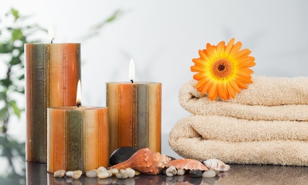 Lighted candles with an orange gerbera on towels and sea shells photo