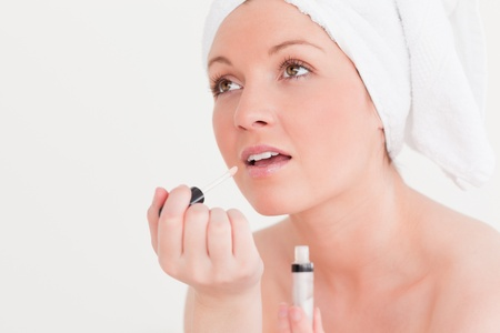 Pretty young woman wearing a towel using a lip gloss against a white background photo