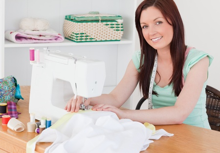 Attractive red-haired female using a sewing machine in her living room photo