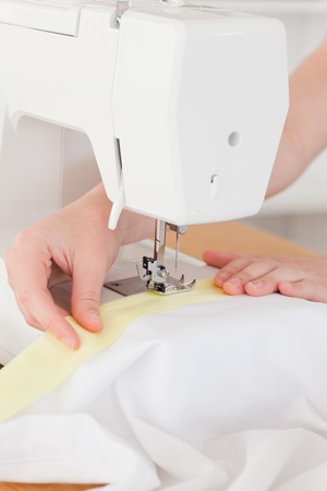 Caucasian hands using a sewing machine in the living room photo