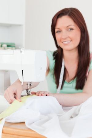 Good looking red-haired female using a sewing machine in her living room photo