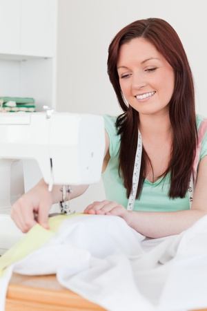 Cute red-haired female using a sewing machine in her living room photo