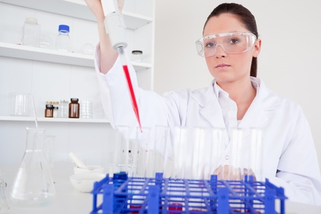 Beautiful female biologist holding a manual pipette with sample from test tubes in a lab Stock Photo - 10071839