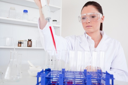 Attractive female biologist holding a manual pipette with sample from test tubes in a lab Stock Photo - 10071851