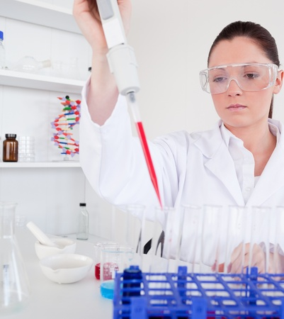 Gorgeous female biologist holding a manual pipette with sample from test tubes in a lab Stock Photo - 10070319