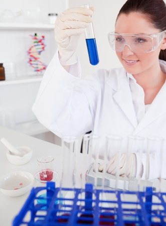 Attractive red-haired woman holding a test tube in a lab photo