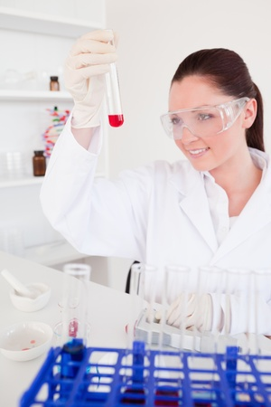 Pretty red-haired woman holding a test tube in a lab photo