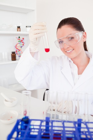 Charming red-haired woman holding a test tube in a lab photo