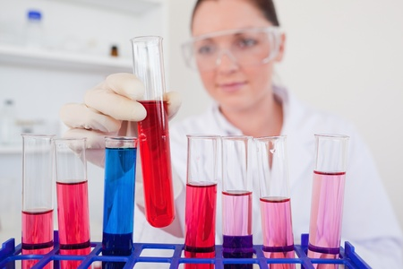 Beautiful red-haired woman holding a test tube in a lab Stock Photo - 10074141
