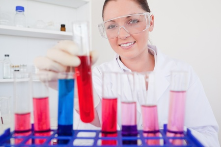 haematologists: Gorgeous red-haired female holding a test tube in a lab
