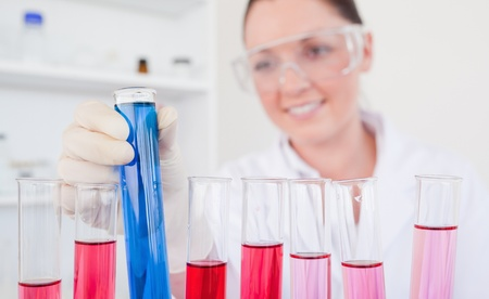 Attractive red-haired female holding a test tube in a lab photo