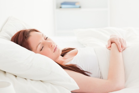 Close-up of a pretty red-haired female sleeping in her bed photo