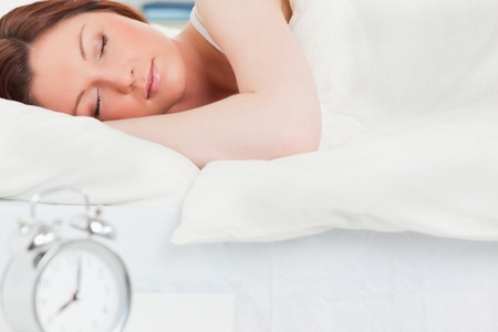 Charming red-haired woman sleeping in her bed photo