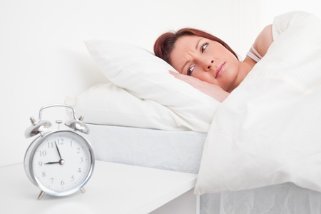 Charming red-haired female waking up thanks to an alarm clock Stock Photo - 10070813