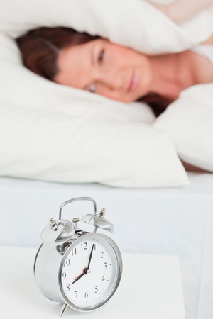 Beautiful red-haired woman waking up thanks to an alarm clock in the bedroom photo