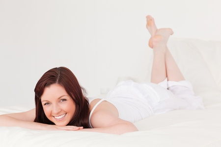Good looking red-haired female having a rest while lying on her bed photo