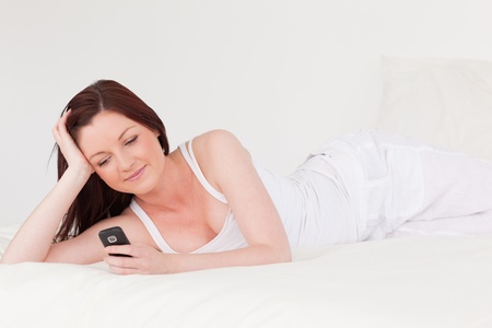 Beautiful red-haired female relaxing with her mobile while lying on her bed photo