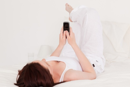 Pretty red-haired female relaxing with her mobile while lying on her bed photo