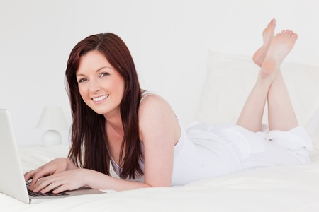 Beautiful red-haired female relaxing with her laptop while lying on her bed photo