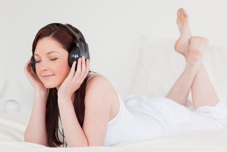 sexy headphones: Pretty red-haired female relaxing with her headphones while lying on her bed