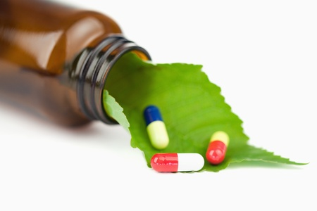 Leaf and pills in a small bottle against a white background Stock Photo - 10069781