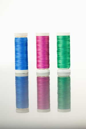 Colorful spools of thread on a table against a white background photo