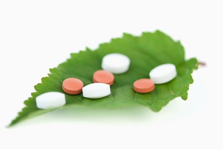 Pills on a leaf against a white background photo