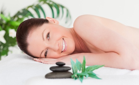 Happy young woman lying on her belly in a spa photo