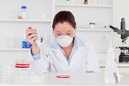 Young scientist preparing a sample while wearing a protective mask Stock Photo - 10071002