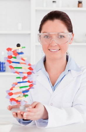 Portrait of a cute scientist showing the dna double helix model photo