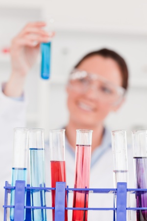 Young scientist looking at test tubes with the camera focus on the tubes Stock Photo - 10071399
