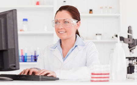 Cute scientist typing a report with her computer photo