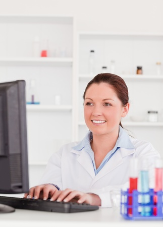 Smiling scientist typing a report with her computer photo