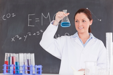 Cute scientist looking at a container filled up with a blue liquid Stock Photo - 10074516