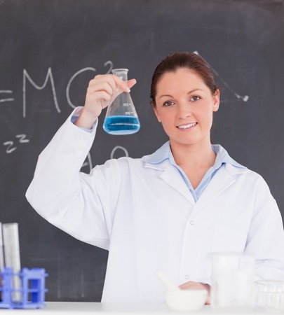 Beautiful scientist showing a container filled up with a blue liquid photo